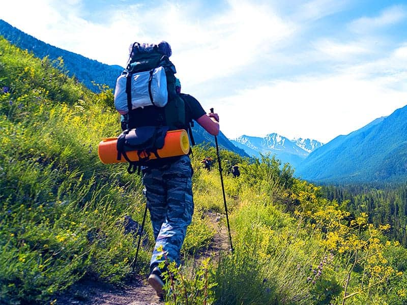 Man hiking mountains with heavy backpack