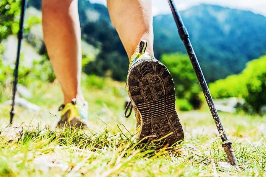 Hiker practicing Nordic walking in nature outdoors