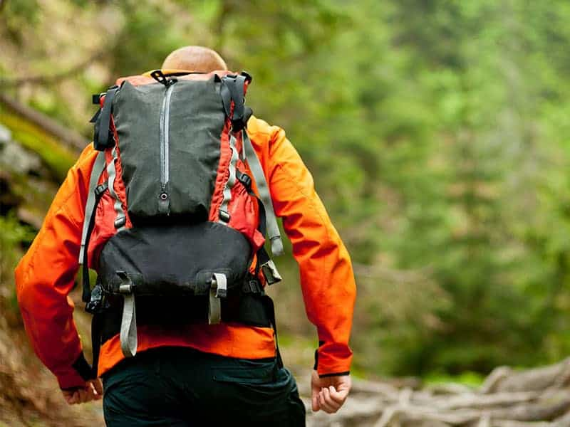 Man in orange jacket hiking outdoors with backpack