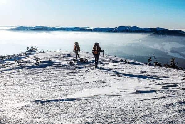 Two men hiking on snowy mountain in winter