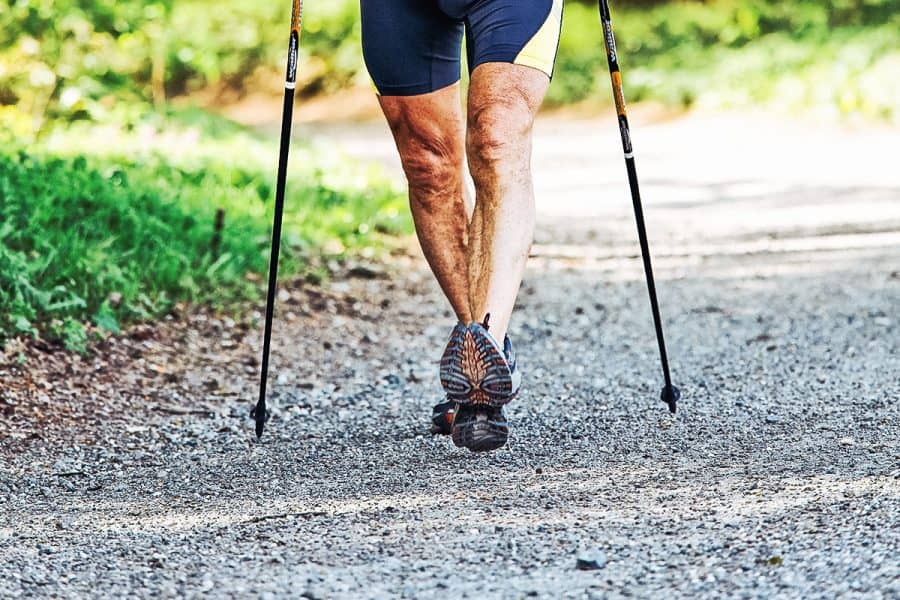A senior doing nordic walking at a brisk pace on a country road