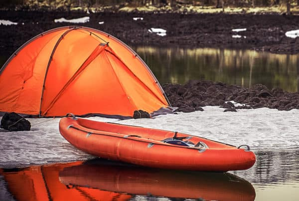 Campsite with orange tent and canoe on a lake