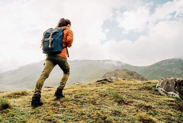 Woman with backpack hiking up a mountain