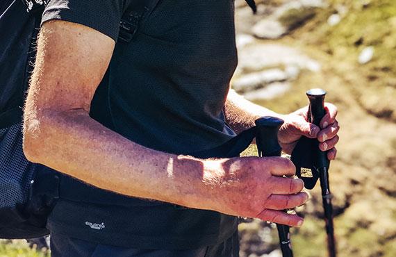 Close-up on hiker's hands holding trekking pole