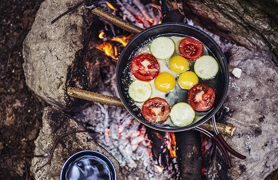 Cooking breakfast on a campfire during a backpacking trip