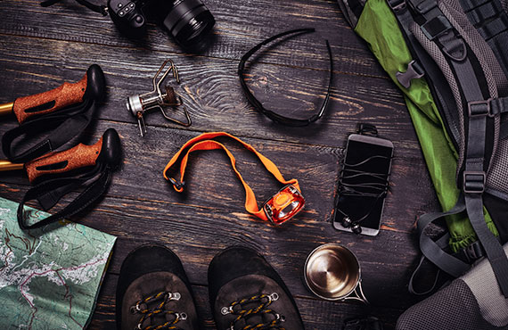 Backpacking accessories set on dark wooden background: backpack, boots, camera, flashlight, map, smarphone and others