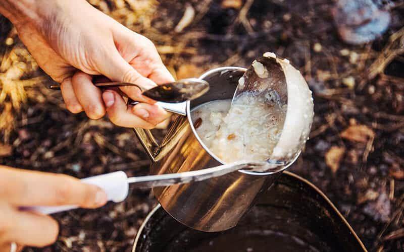 Hiker cooking porridge for breakfast in a campsite