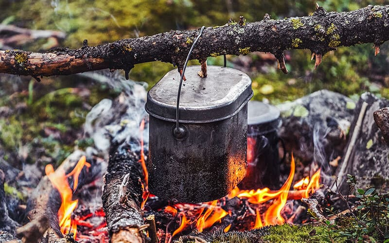 Cooking dinner in a pot over the fire in the backpacking camp