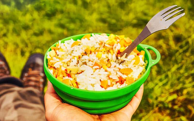 Hiker eating his backpacking lunch in a silicone plate