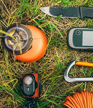 Backpacking survival kit gear on grass