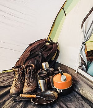 Interior view of a dome tent set up for camping with backpacking gear