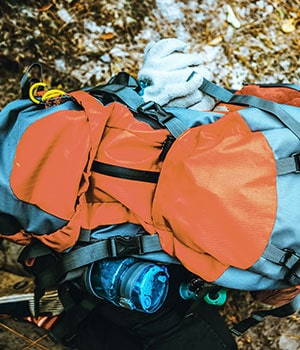 Picture of a comfortable orange backpack lying on the rocks outdoor