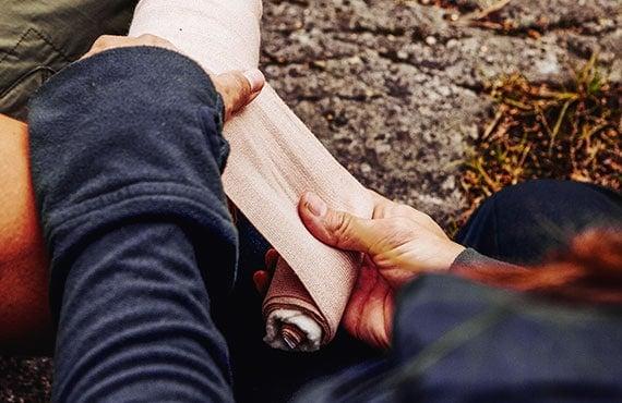 Hiker applies a ankle tensor bandage