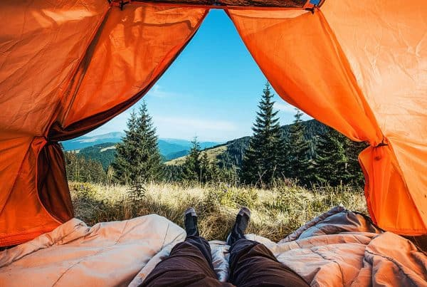 Legs of a hiker in a tent enjoying a mountain landscape during an adventure trek
