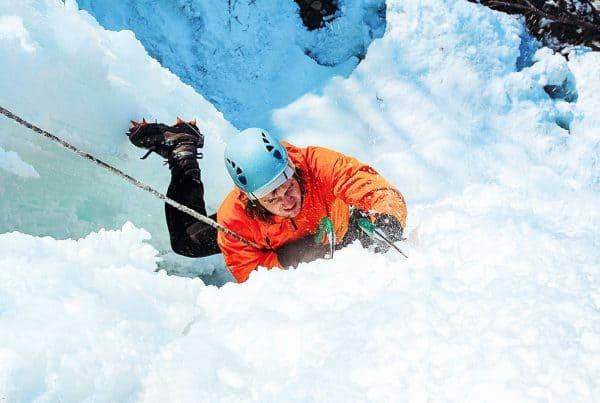 Alpinist ice climbing a steep frozen waterfall
