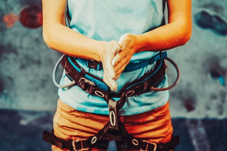 Close-up on intermediate climber tying her shoelace